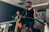 Woman Giving Instruction To Male Runner On Treadmill In Laboratory. Runner With Mask On Treadmill In poster