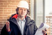 An Angry Disgruntled Builder Worker In A Helmet With Project Drawings Plans In His One Hand And Mobi poster