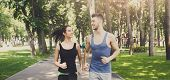 Young Happy Sporty Couple Jogging In Green Park During Morning Workout, Copy Space, Crop poster