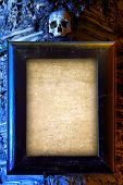 stock photo of empty tomb  - Old wooden frame and empty blank paper hanged on a wall with skull on top - JPG
