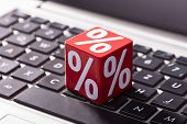 Close-up Of Percentage On The Red Wooden Block Over The Laptop Keypad poster