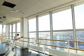 Male Dancer Doing Leg Stretching Near Window At Gym Studio. Young Person Wears White Suit. Concept O poster
