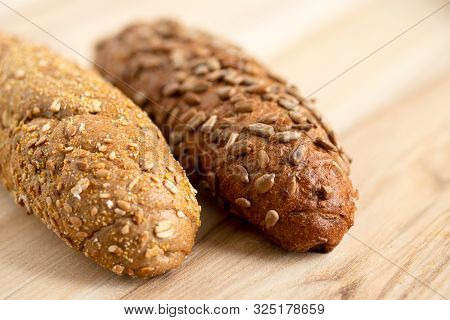 poster of Long Whole Wheat Sunflower Seed Bread Roll And Long Whole Wheat Sesame Seed Bread Roll On Light Wood