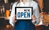 Woman Barista Wear Jean Apron Holding Come In We Are Open Sign On Tablet To Customer At Bar Counter  poster