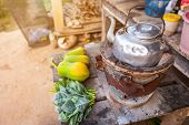 Old Thai Kettle On Thai Charcoal Stove With Green Leafy Vegetables And Papaya Put On A Wooden Table poster