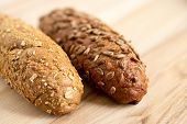 Long Whole Wheat Sunflower Seed Bread Roll And Long Whole Wheat Sesame Seed Bread Roll On Light Wood poster