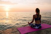 Yoga At Sunrise. Attractive Woman In Sportswear, Is Engaged In Yoga, Sitting On Pier In Lotus Pose,  poster