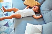 Beautiful toddler child girl wearing white bodysuit crying lying down on the sofa poster
