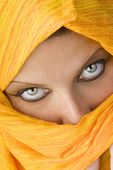 stock photo of burka  - attactive and strong eyes behind an orange scarf used like a burka - JPG