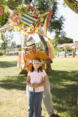 image of pinata  - Hispanic girl being blindfolded next to pinata outdoors - JPG