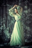 A full length portrait of a mysterious lady in a light turquoise dress posing indoor. Fairy tale, be poster