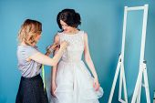 Seamstress Woman And Bride Discuss The Details Of Wedding Dress In The Studio On A Blue Background . poster
