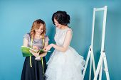 Seamstress Wedding Consultant And Bride Discuss The Details Of Wedding Dress In The Studio On A Blue poster