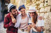 Happy Group Of Tourists Traveling And Sightseeing Using Phone. poster