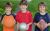 stock photo of young boy  - Three Little Boys Each Holding Sports Balls - JPG
