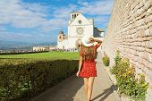 Tourism In Italy. Back View Of Beautiful Girl Walking Towards The Basilica Of Saint Francis Of Assis poster
