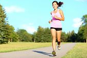 stock photo of short legs  - Sport fitness woman running in park on summer day - JPG
