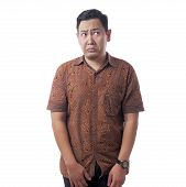 Portrait Of Young Asian Man Wearing Batik Shirt Shows Stunned Worried Expression, Side Glance Gestur poster