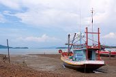 Traditional Thai fishing boats on a beach during low tide, Koh Phangan island, Thailand. poster