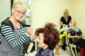 Smiling hairdresser makes hair styling for woman by rake-comb and looks at camera in beauty salon; f