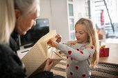 Little girl wearing sweater and opening christmas present at home. Curious granddaughter open birthd poster