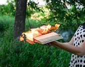 Burning Book In The Hands. Burning Books In The Forest. The Girl Holds A Burning Book In Her Hands.  poster