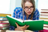 picture of bookworm  - Portrait of thrilled girl in eyeglasses looking at camera while reading book - JPG