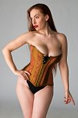 image of bustiers  - Pretty young redhead in a copper and brass corset - JPG