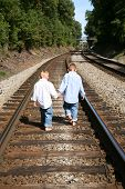picture of walking away  - Two young boys walking on railroad tracks - JPG