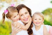 Picture of young mother hugging two little children, closeup portrait of happy family, cute brunette