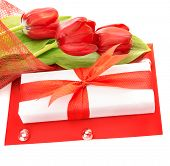 Picture of white gift box with red ribbon, fresh tulips flower bouquet, paper card, greeting postcar