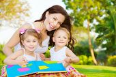 foto of daycare  - Image of cute young female with two little children read book outdoors - JPG
