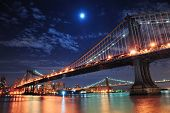 stock photo of bridges  - Brooklyn Bridge and Manhattan Bridge over East River at night with moon in New York City Manhattan with lights and reflections - JPG