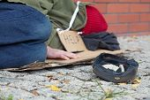 foto of beggar  - Beggar falling asleep on the street with a cap for collecting money - JPG