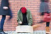 stock photo of begging  - Homeless man sitting on a street passed by people - JPG