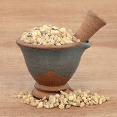 stock photo of pestle  - Frankincense in a mortar with pestle over papyrus background - JPG
