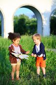 stock photo of spinner  - The boy shows a wind spinner to the girl - JPG