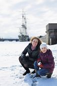 foto of snowball-fight  - Mother and daughter playing a snowball fight against a sailboat - JPG