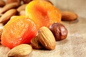 picture of filbert  - Closeup of dried apricots lying near almonds and filbert nuts on wooden background - JPG