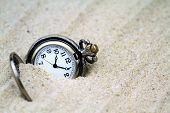 pic of wind up clock  - Antique pocket watch buried in sand - JPG