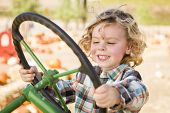 picture of riding-crop  - Adorable Young Boy Playing on an Old Tractor in a Rustic Outdoor Fall Setting - JPG