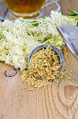 stock photo of meadowsweet  - Metal sieve with dried flowers of meadowsweet a bouquet of fresh flowers of meadowsweet tea in a glass cup on a background of wooden boards - JPG