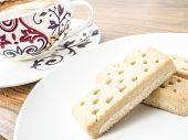 stock photo of shortbread  - Shortbread fingers on the white plate and coffee cup in background - JPG