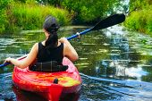stock photo of paddling  - Girl with paddle and kayak on a small river in rural landscape - JPG