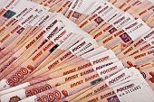 Heap of five thousand Russian rubles banknotes surface top view background
