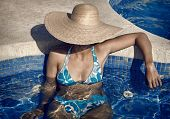 Lady With Straw Hat And Bikini In The Pool