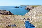Постер, плакат: Mans Legs Relaxing On The Rocky Coast Of Southern Wales