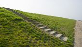 stock photo of dike  - Stony stairs on a dike along a road - JPG