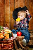 stock photo of baby cowboy  - Little Cowboy on a farm in a hat and jeans after harvest - JPG