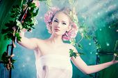 pic of loach  - Beautiful young woman standing under an arch of flowers and overgrown loach - JPG